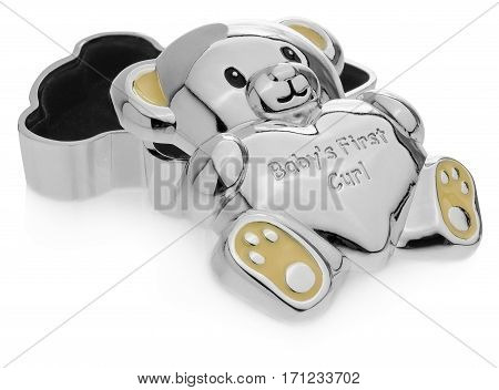 Silver box in the shape of a teddy bear to the first baby teeth. The Children souvenirs lined inside with black velvet. Ears and feet in yellow on a white background with slight reflection. Toy box open lerzy on a white background with slight reflection.