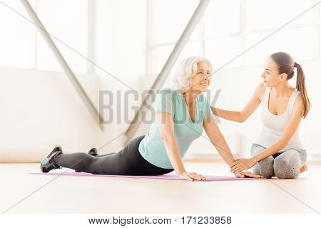 Staying fit. Positive cheerful elderly woman lying on a yoga mat and exercising on it while training in the fitness centre