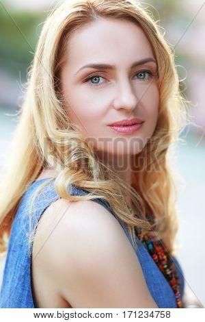 beautiful adult blond woman portrait outdoor backlight