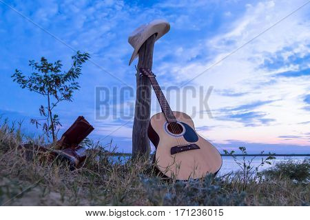 Guitar resting on a post waiting for it's owner at sunset.