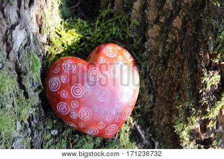 Red heart of stone with milled patterns, various white circles, Lies between two thick brown-gray oak trees on a tree stump with green moss and is partly irradiated by the sun, In February 2017 in the Visch Valley