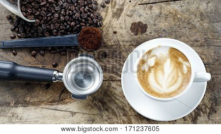 Latte art. Cappuccino coffee. A cup of latte, cappuccino or espresso coffee with milk put on a wood table with dark roasting coffee beans. Drawing the foam milk on top.