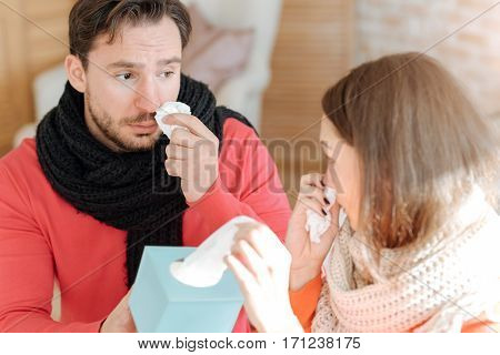 Caring about each other. Ill empathetic young couple sitting in the bedroom and suffering from influenza while holding box with handkerchiefs and expressing care
