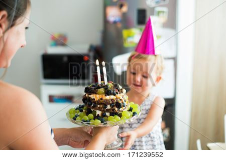 Beautiful young smiling mother giving her daughter fruit birthday cake with two candles. Pink party hat on head.