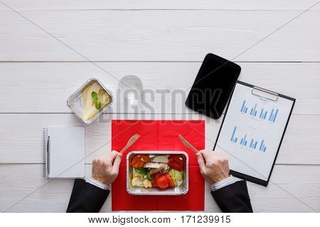 Business lunch at working place. Businessman in office. Healthy, diet restaurant food delivery in foil boxes: turkey with vegetables. Tablet pc and papers. Top view, flat lay on workspace
