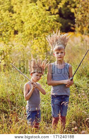 Two Brothers have a crown from dry grass on the head and swords in hands. Joy and play concept
