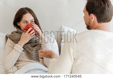 Treating each other . Young involved charming couple sitting on the bed at home while expressing love and drinking tea