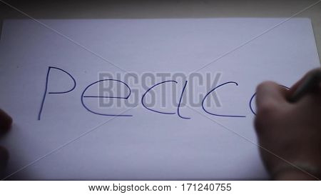 hand of a young man writes the word peace on a white sheet of paper