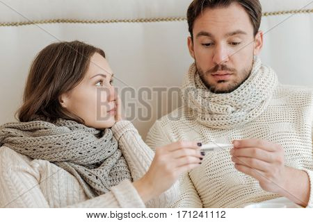Suffering from temperature. Ill young upset couple sitting on the bed at home and holding the thermometer while expressing disappointment