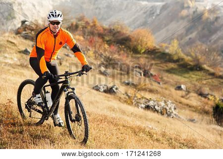 Cyclist Riding the Bike on the Beautiful Spring Mountain Trail. Cyclist in the helmet and the gkasses. Travel in the countryside. Beautiful landscape with hill and rock.