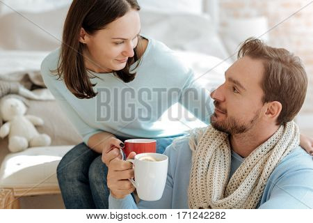 Caring about our health. Delighted involved smiling couple sitting in the bedroom while expressing care and drinking hot tea with lemon