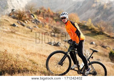 Cyclist in Red Jacket Riding the Bike Rocky Hill. Extreme Sport Concept. Space for Text. Cycler in the helmet and glasses. Travel in the countryside. Spring season.