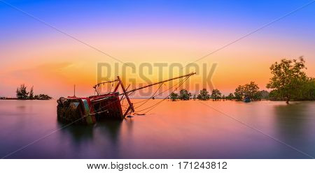The old fishing boat capsized on sea at sunset in Phuket Thailand.