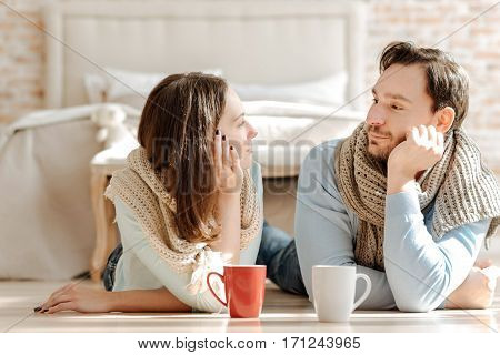 Love you. Peaceful infatuated young couple lying on the floor at home while expressing love and drinking hot tea