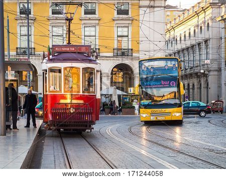 LISBON PORTUGAL - JANUARY 10 2017: Transport in Lisbon: typical old tram and a touristic bus on the Praca do Comercio (Commerce Square).