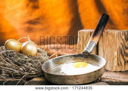 Fried egg on frying pan next to uncooked golden eggs in a nest