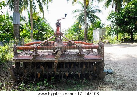 Parking rotary harrow plow at a corner of countryside 's house