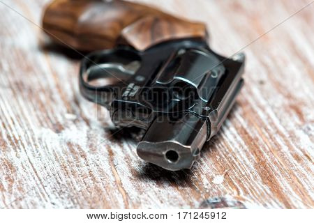 small revolver lying on a wooden table, shallow depth of field