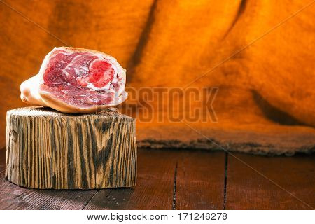 Piece of pork on the wood block over fire light background