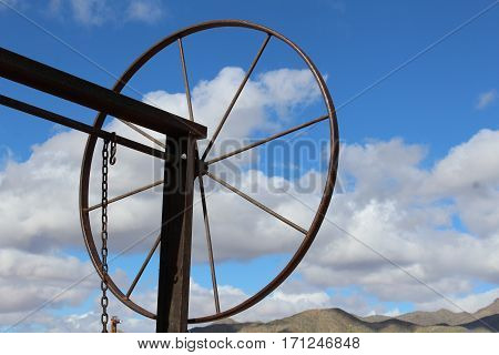 Metal wheel against partly clouded blue sky