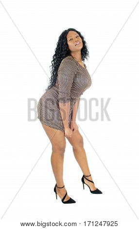 A beautiful African American woman standing in a short dress and pulling it down isolated for white background.