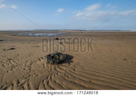 Peaceful scene at Belhaven Bay in Scotland at low tide with patterns and textures of rippled sand and an ancient round stone