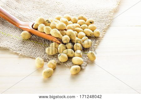 Coated peanuts seaweed flavor with wood spoon on hemp sack wooden table