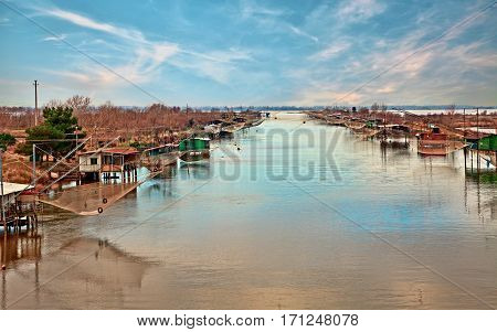 Comacchio, Ferrara, Emilia Romagna, Italy: landscape of the wetland with fishing huts and nets in the lagoon