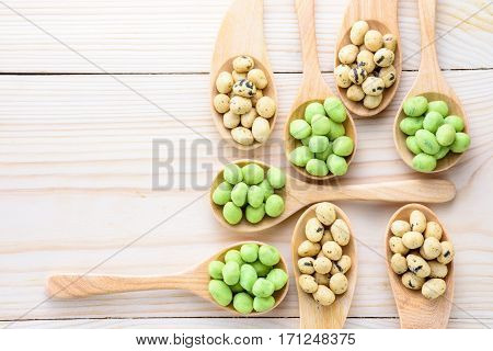 Coated peanuts seaweed and wasabi flavor in wood spoon on wooden table
