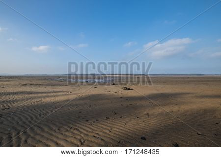 Scottish beach scene at Belhaven Bay in winter at low tide with patterns and textures of rippled sand and blue sky