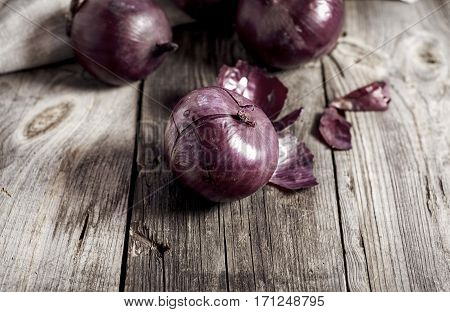 Red onions in the husk on the gray wooden surface close-up