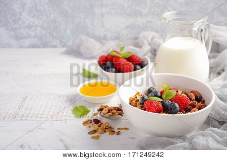 Homemade granola with fresh berries on white wooden background, selective focus, copy space