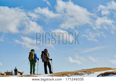 hikers with backpack on the trail in the Carpathians mountains at winter. Hikers on a blue sky background.