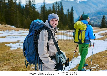 hikers with backpack on the trail in the Carpathians mountains at winter. Hikers on a forest background.