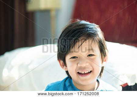 Close up of cute asian boy play and smiling in home.