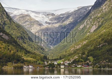 Traditional norwegian fjord village with glacier. Hardanger route. Horizontal