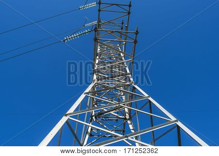 Supports High-voltage Power Lines Against The Blue Sky. View From The Bottom Up