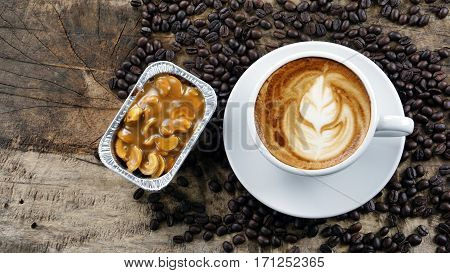 Cappuccino coffee and latte art. A cup of latte, cappuccino or espresso coffee with milk put on a wood table with dark roasting coffee beans. Drawing the foam milk on top.