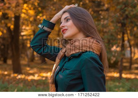 girl stands sideways in the Park and holds hand hair