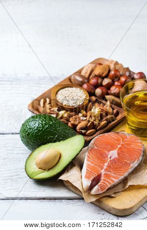 Selection of healthy fat sources food, salmon fish avocado olive oil nuts sesame on a white rustic wooden table. Copy space background