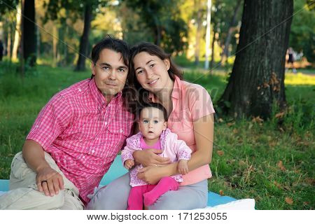 Happy couple with their beautiful daughter in summer park having good time together