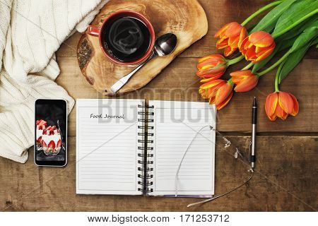 Overhead shot of an open food journal book with cell phone coffee and flowers over a wood table top ready to plan diet. Flat lay top view style.