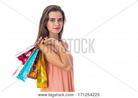 a young girl stands sideways and holding a colorful shopping bags isolated on white