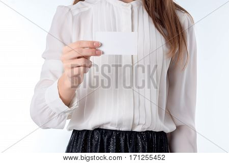a girl holds before a white paper leaf