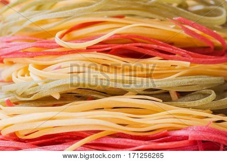 Italian pasta, three color from durum wheat with vegetables on the kitchen textiles, background, selective focus, close-up