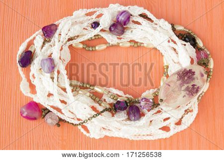 Handmade crocheted cotton organic lace wreath. White crochet frame pattern handicraft background needlework creative craft. Bright crochet wreath with flowers amethyst jewelry place for text