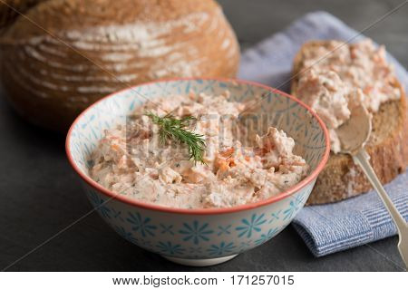 Bowl of fresh fish pate beside sliced bread and spoon with pate and round bread loaf