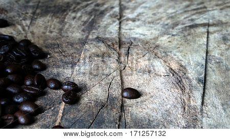 Dark roasting coffee beans on the wood table.