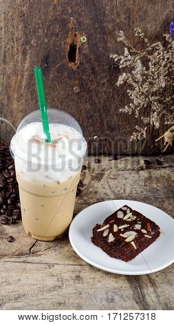 Ice cappuccino coffee and sweet chocolate brownies cake. A cup of latte, cappuccino or espresso coffee with milk put on a wood table with dark roasting coffee beans.
