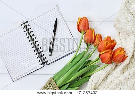 Overhead shot a bouquet of orange and yellow tulips and a cozy knit throw blanket over white wood table top with an open book and pen ready to journal. Flat lay top view style.